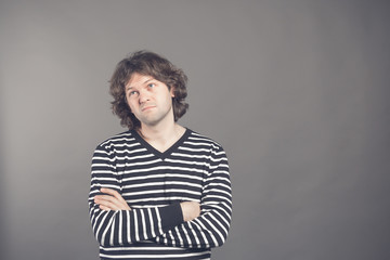 Studio shot of pensive young European male with voluminous hair posing at blank wall, keeping arms crossed and looking up with thoughtful expression, making plans for weekend. Body language