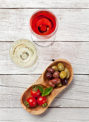 White and rose wine glasses with olives and tomatoes