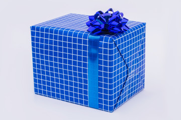 Blue gift box with white decor. Present box wrapped in dark blue wrapping paper with bow. Christmas surprise concept.