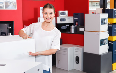 Young attractive saleswoman offering home safe in specialty shop