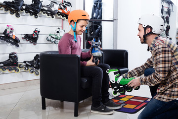 father assisting son in trying on roller-skates in sports store