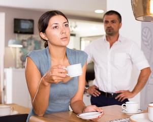 Upset woman drinking tea with disgruntled man