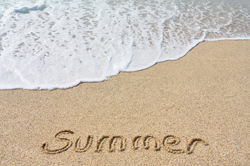 Summer inscription on a tropical sandy beach with blue sea, waves and foam on a background.