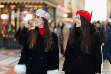 Two attractive smiling young women are shopping in the city