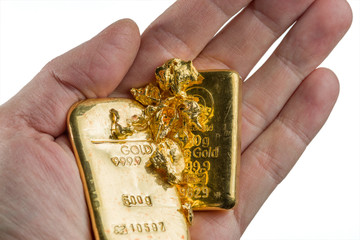 Two gold bars and several gold nuggets on the palm. Isolated on white background.