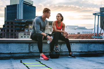Fitness couple sitting on rooftop during workout