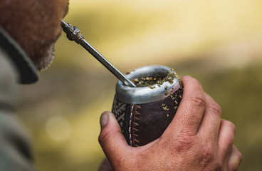Middle aged man drinking yerba mate in nature. Travel and adventure concept. Latin American drink yerba mate