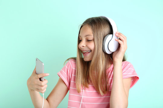 Beautiful young girl with headphones and smartphone on mint background