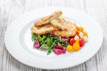 Grilled chicken breasts with sesame, salad with cabbage fat and rucola on light wooden background. Hot Meat Dishes