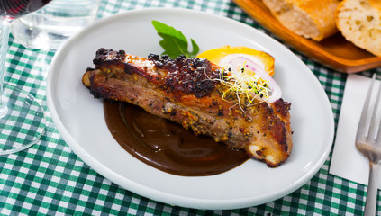 Roasted pork ribs in chocolate sauce with baked potatoes