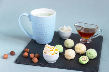 Fat keto peanut butter, cheesecake, matcha balls and keto matcha coconut bulletproof tea in blue cup. keto protein balls and matcha tea recipes ingredients. it works ketogenic diet. blue background