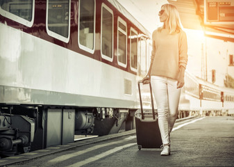 Blonde woman with her luggage go near the red train