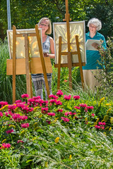 Two women painting on canvas in garden.
