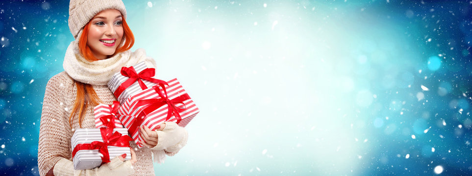 Christmas and New Year holidays. Happy readhead woman with gifts. Shopping woman holding gift boxes on winter background with snow. Sale poster with copy space.