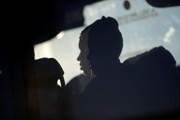 A migrant woman is silhouetted as she sits in a bus after arriving on a rescue boat at the port of Malaga