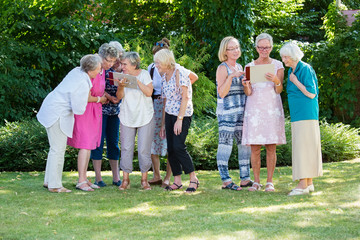 Group of senior women looking at pictures.