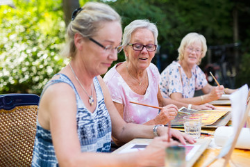 Retired senior women painting together outdoors as group recreational and creative activity during summer.