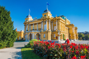 Zelfklevend Fotobehang Theater Croatia, Zagreb, beautiful historic national theater building and flowers in park, blue sky, summer day, popular tourist destination