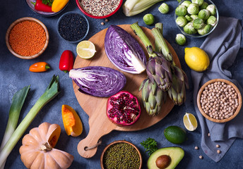 Healthy vegan food, cooking ingredients with fresh vegetables, quinoa, lentils, chickpeas, clean eating concept, flat lay