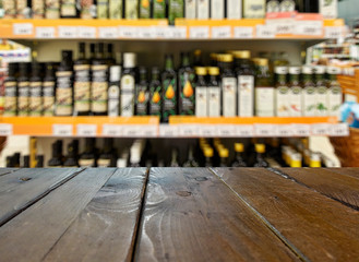 Grocery store. Shelves with olive, rapeseed and sunflower oil. Defocused, blurred image.