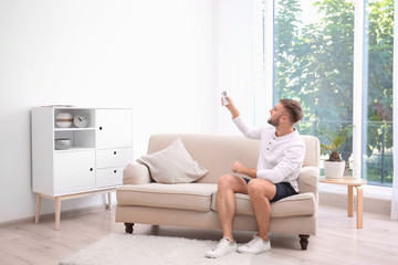 Young man with air conditioner remote at home