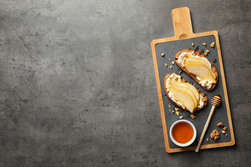 Toasted bread with tasty cream cheese and pear on gray table, flat lay. Space for text