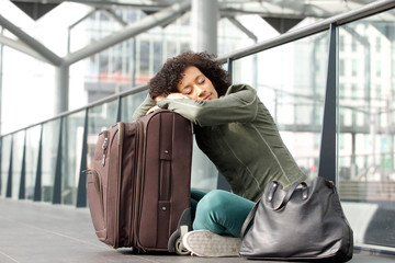 african american woman sleeping at station with luggage