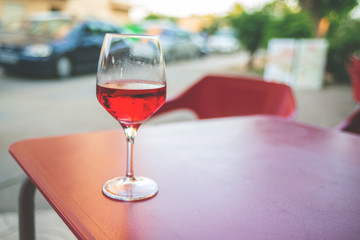 Glass of rose wine on the table in street cafe Vintage toning Selective focus Copy space