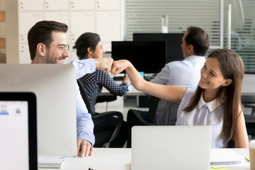 Friendly smiling colleagues fist bumping at workplace, happy coworkers sharing success, young woman and man celebrating good teamwork result, satisfied by collaboration, cooperation at work, respect