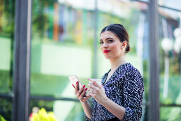 Woman using phone near office