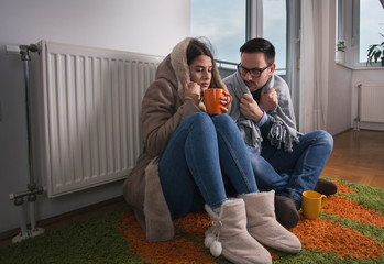 Obraz Couple sitting beside radiator and freezing - fototapety do salonu