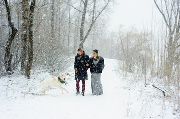 Winter walk in a snowstorm with a dog