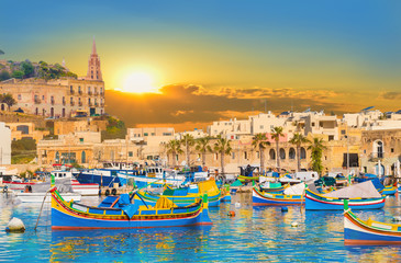 Marsaxlokk village harbor of Malta, illuminate by sunset light Wall mural