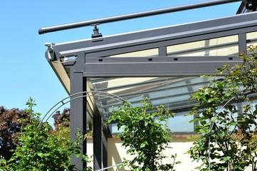 Verglaster Wintergarten mit beschichtetem Metallrahmen, Windmesser und Glasdach, umgeben von Rosenbögen an einem Wohnhaus