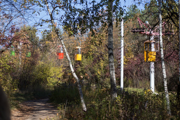 multicolored cable car cabins, funicular, moving through the autumn forest