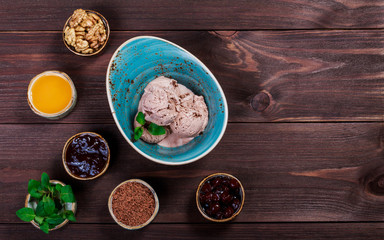 Chocolate ice cream scoops in bowl with mint leaves on wooden background. Top view