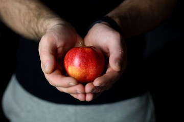 Male hands holds and gives a fresh juicy red apple, offering healthy nutrition food and diet, on a black background