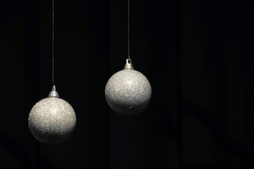 Two hanging silver Christmas balls on dark background