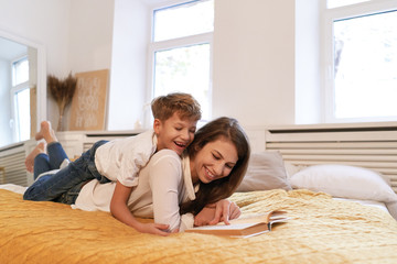 Smiling mother and son embracing and reading book together