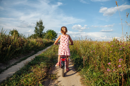 Little girl riding a bike on a rural road