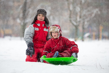 Two boys riding at the slide on snowy park
