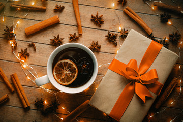 Cup of tea with Christmas ingredients and gift box on wooden background