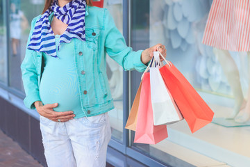 Beautiful pregnant woman with paper packages near the mall
