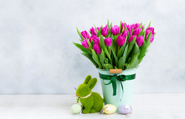 Violet fresh tulip flowers in pot with easter bunny on gray background with copy space