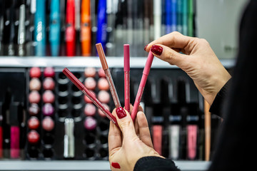 close-up seller hands demonstrating different eyeliners in beauty store