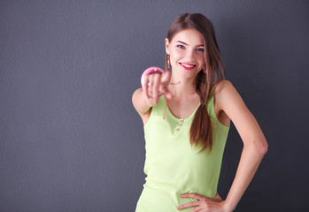 Portrait of a young smiling woman on a gray wall background