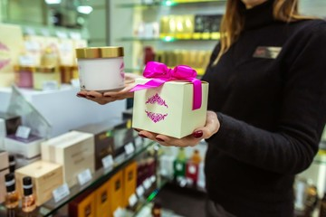 salesgirl offering cosmetic gift set in perfume and cream shop. profitable purchases on sale