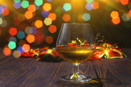 Glass of whiskey or brandy on wooden table on bright glowing background