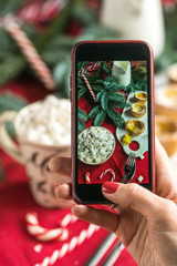 The hands of the girl with the phone make a photo of the New Year mood. Cocoa, marshmallows, cup, spruce, red cloth.