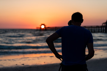Naples, Florida red and orange sunset in gulf of Mexico with sun setting inside Pier bokeh, back of young man photographer videographer taking pictures filming landscape